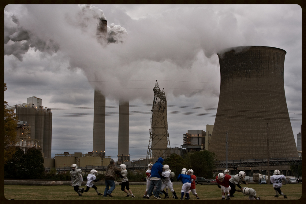 """beneath the plume"" A local youth football league practices beneath the American Electric Power Gen. James M. Gavin coal-burning power plant in Cheshire, Ohio. As the global climate change debates intensifies around the world, living in close proximity to coal burning power plants is a daily reality for many communities in the rural United States. The James Gavin power plant is located literally the middle of the town of Cheshire, Ohio. It is the largest power plant in Ohio, and burns up to 2,500 tons of coal per day at full capacity.  photo credit: kayana szymczak"