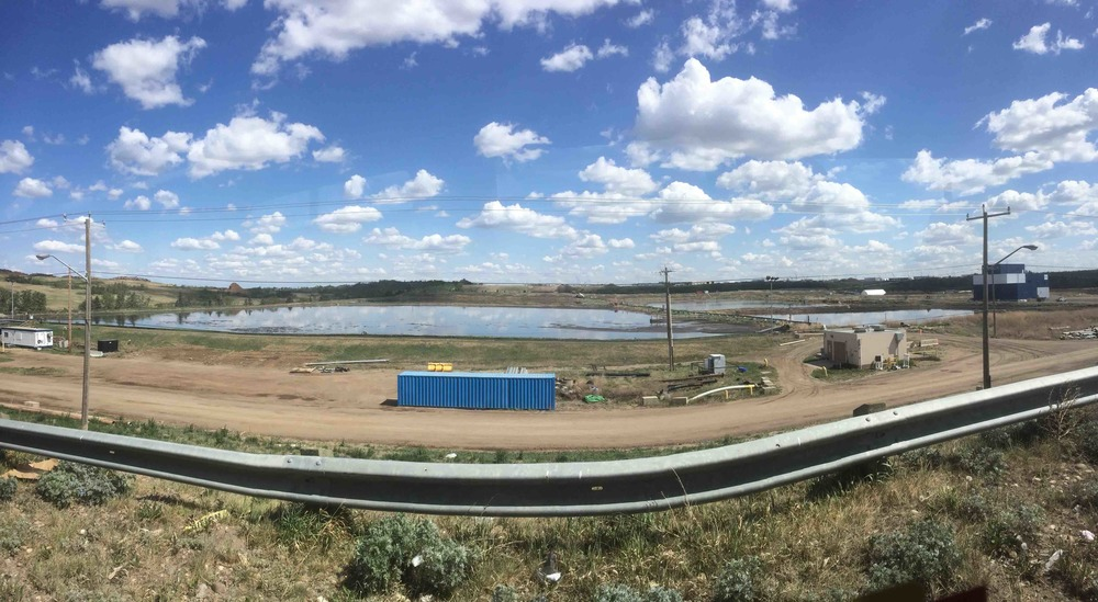Biosolids storage lagoons at Edmonton Waste Management Centre, with the blue-and-white struvite recovery system building at right.