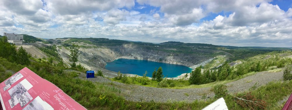 Looking northwest at the open-air Jeffrey Mine from a small park at the north edge of the town of Asbestos, QC. Note the plateaus of mine tailings - a total of ~800 hectares (1977 acres) - in the distance.