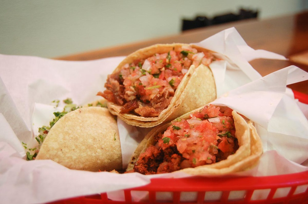 Pork, cabeza, and chorizo tacos at La Taqueria | Photo Credit: stu_spivack [Flickr]