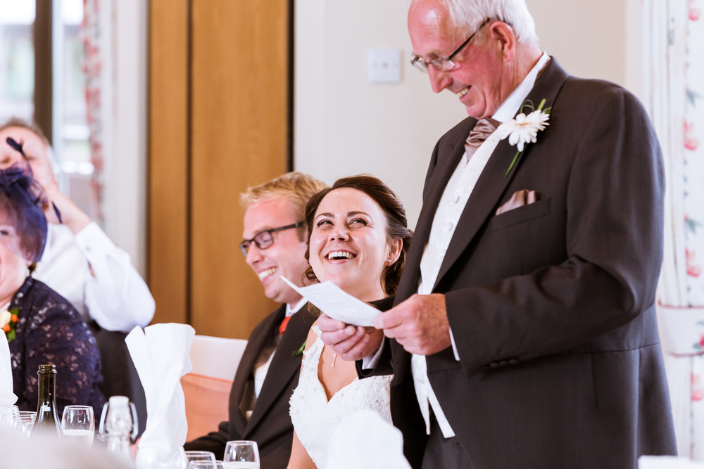 The Bride looking to her father as he delivers his speech, they are both laughing