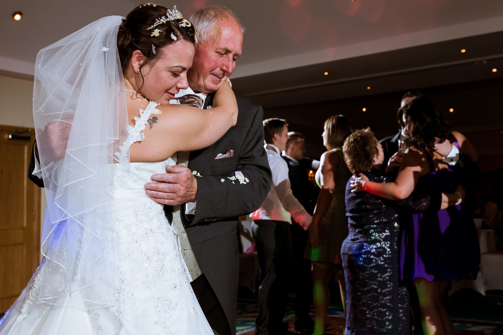 The bride is dancing with her father, this happened just after her first dance with her husband
