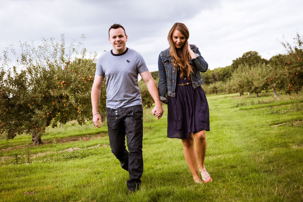 Dan & Kerry Walking through an orchard hand in hand at the start of their Portrait Session
