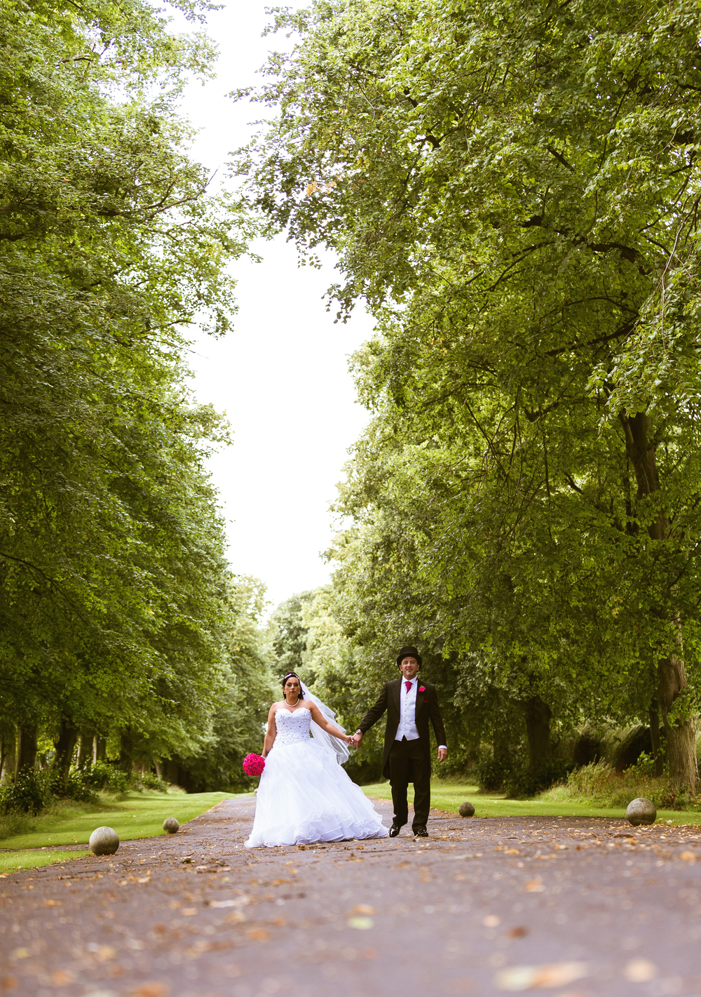 A wedding photo of the bride and groom walking towards their reception at Knowlton court to great all their guests
