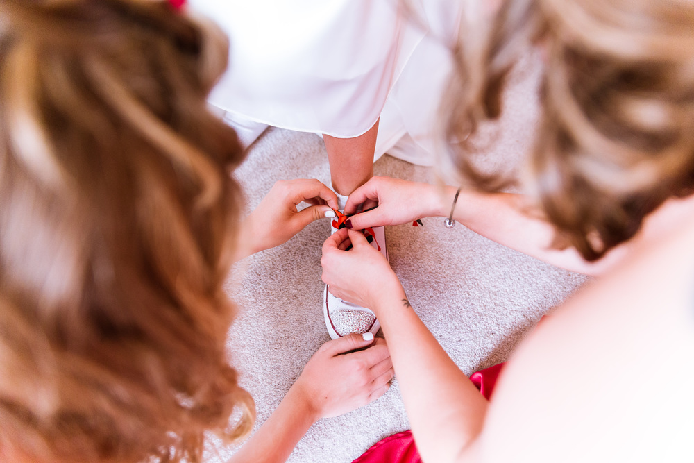 Liann's daughters helping her put her shoes on before her wedding, as she could not bend down and tie them up herself