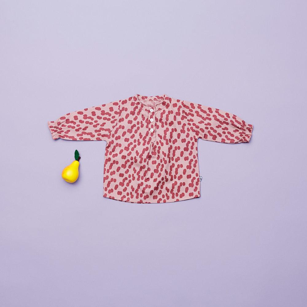 En af vores favoritter i denne samling til piger i størrelse 74, er den flotte printede skjortebluse med knapper og rynk på ærmerne. Den er fin som et sæt med de matchende bukser eller med en anden underdel.