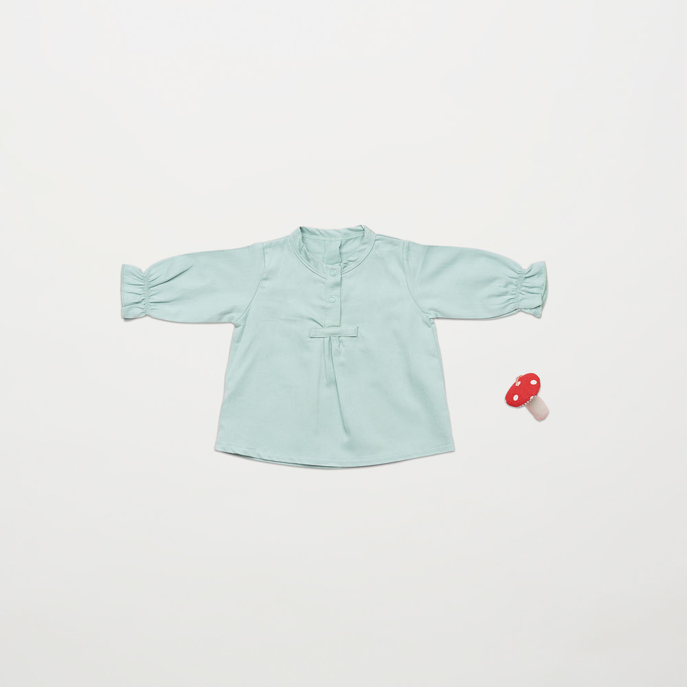En af vores favoritter i denne samling til pigerne i størrelse 62, er den søde skjortebluse med rynker og knapper.