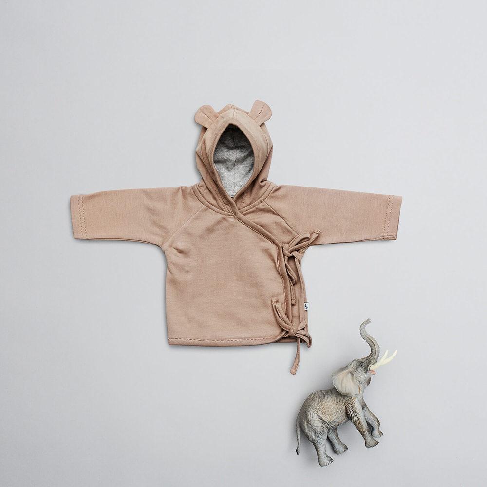 En af favoritterne i Newborn kollektionen er denne søde cardigan med bindebånd. Den er let at tage af og på, og din baby kan putte sig lunt og trygt med den lille hætte.