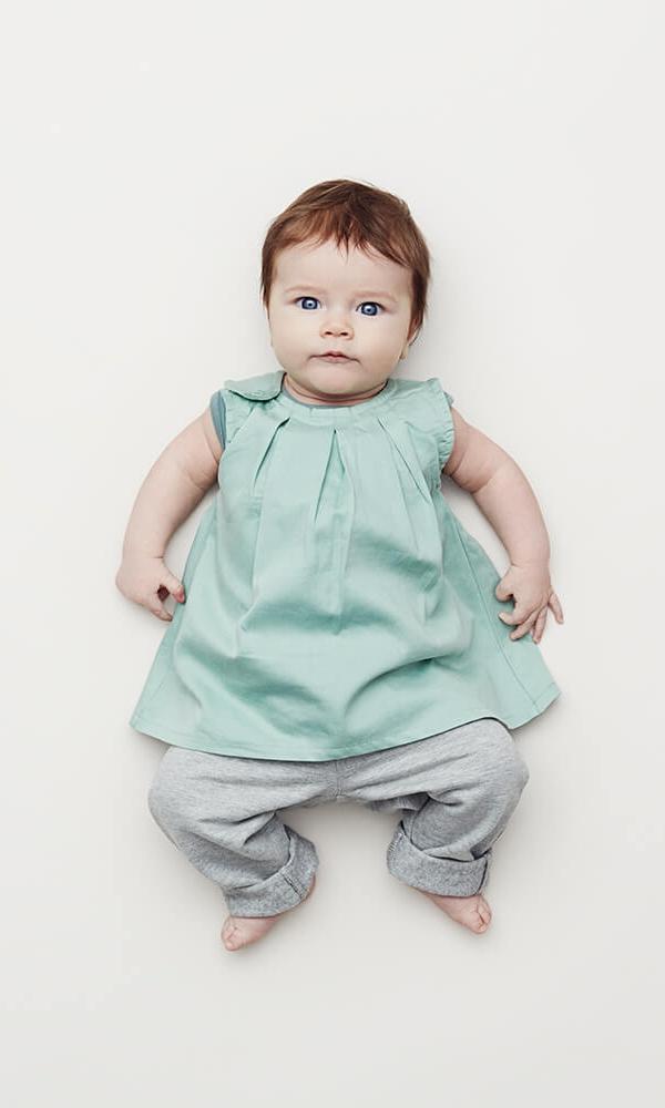 Din datter kan nu løfte hovedet og begynder at følge med. Bemærk den viste kjole er med i sommerblanding i str. 56.