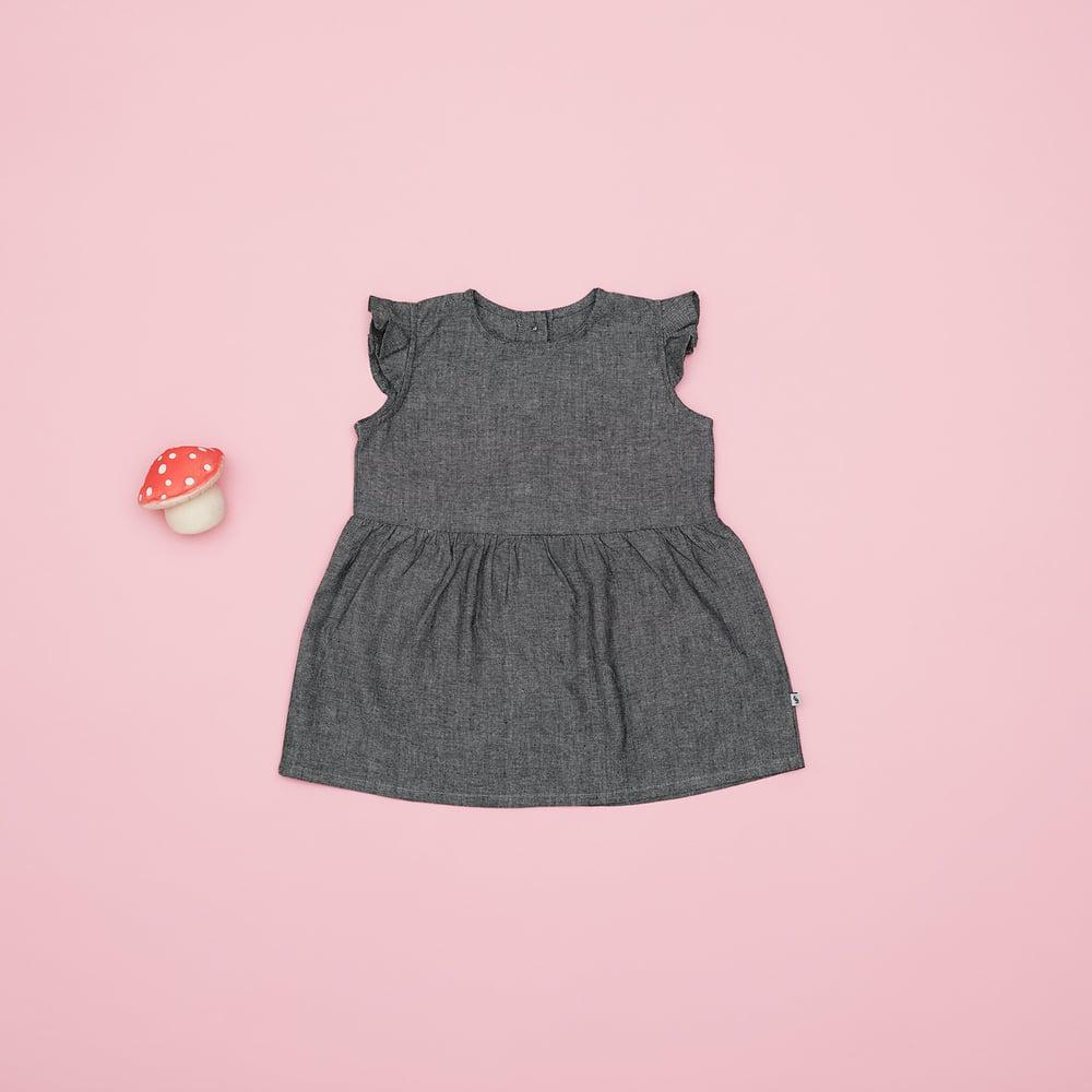 En af favoritterne til de store piger i størrelse 86 er denne søde kjole med knapper og flæser.