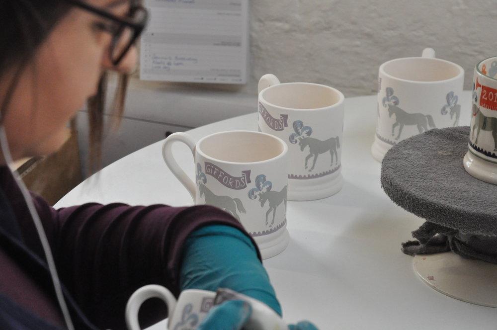 Charlotte decorating the 2018 mugs in the decorators studio
