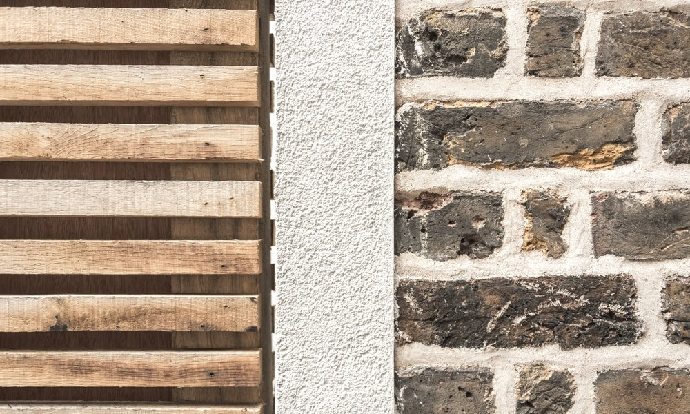 A simple palette of materials is used at the rear; oak slats, rendered woodfibre and lime mortar to retained brickwork.