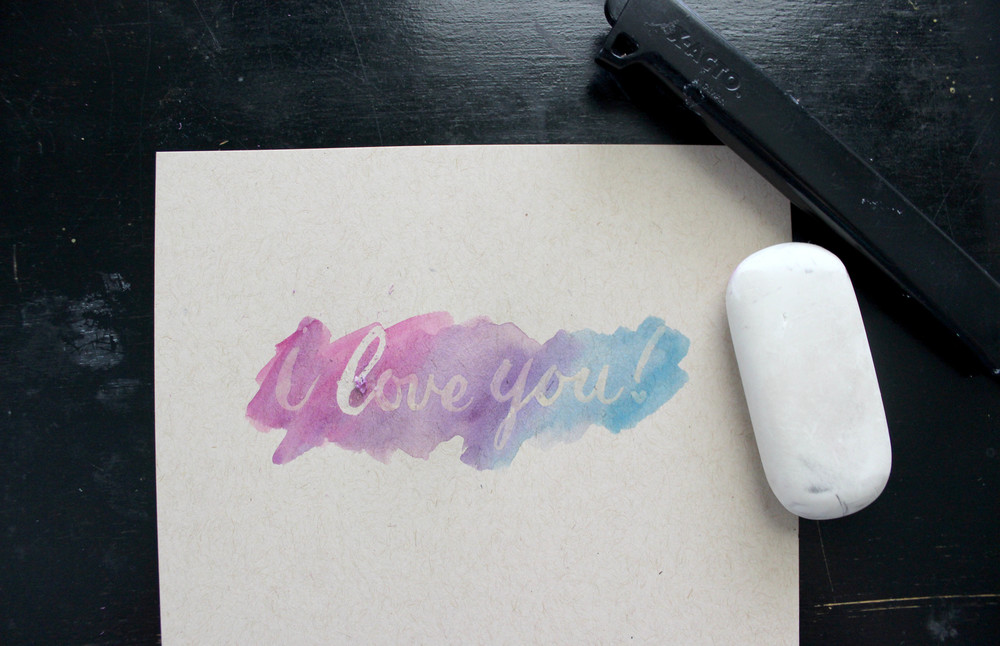 Ashley Bush shows how to letter with masking fluid and apply a watercolor wash overtop