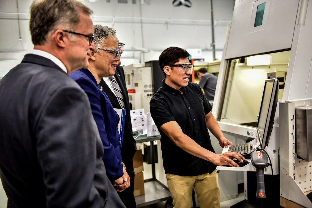 Alexis Ojeda, a program apprentice, explains the high-tech nature of today's manufacturing to DuPage County Board Chairman Dan Cronin (left), President Preckwinkle (right) and others on a tour of the facility.