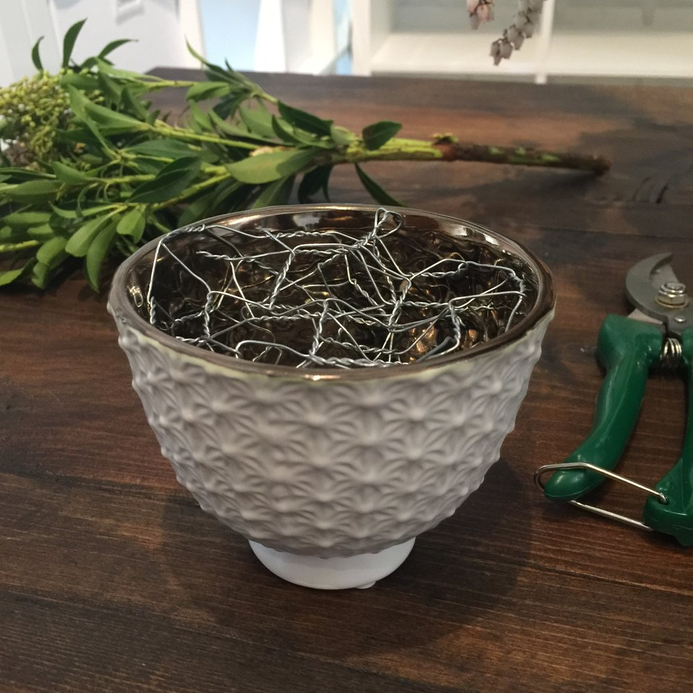 1 - Start by creating a cage out of chicken wire or by criss-crossing floral tape over the opening of the container.