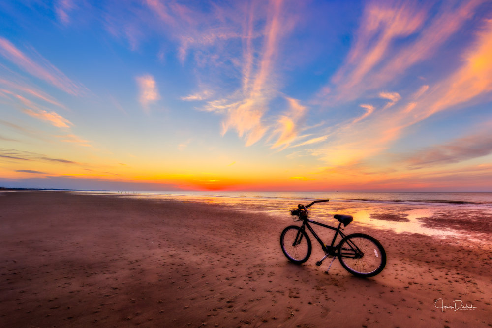 A biker paused to watch the sun appear on the horizon at Hilton Head.