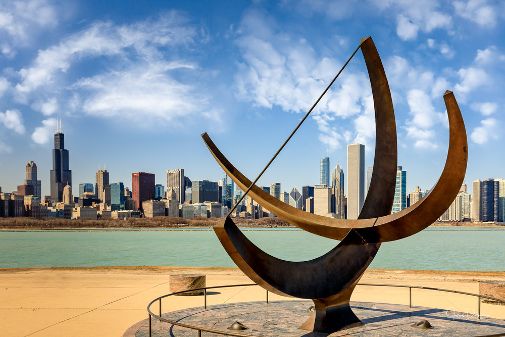 The Chicago skyline as seen from Adler Planetarium.  Man enters the Cosmos sundial is in the foreground.