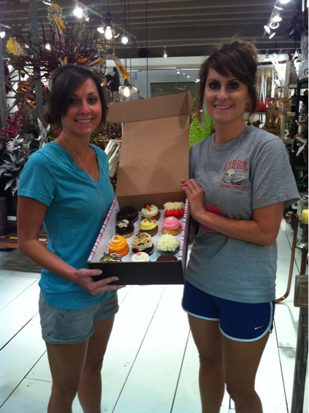 Heidi and Hayley with cupcakes setting up the Dallas showroom