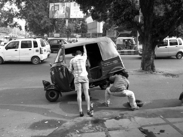Bradley holding up a taxi in India while driver changes tire