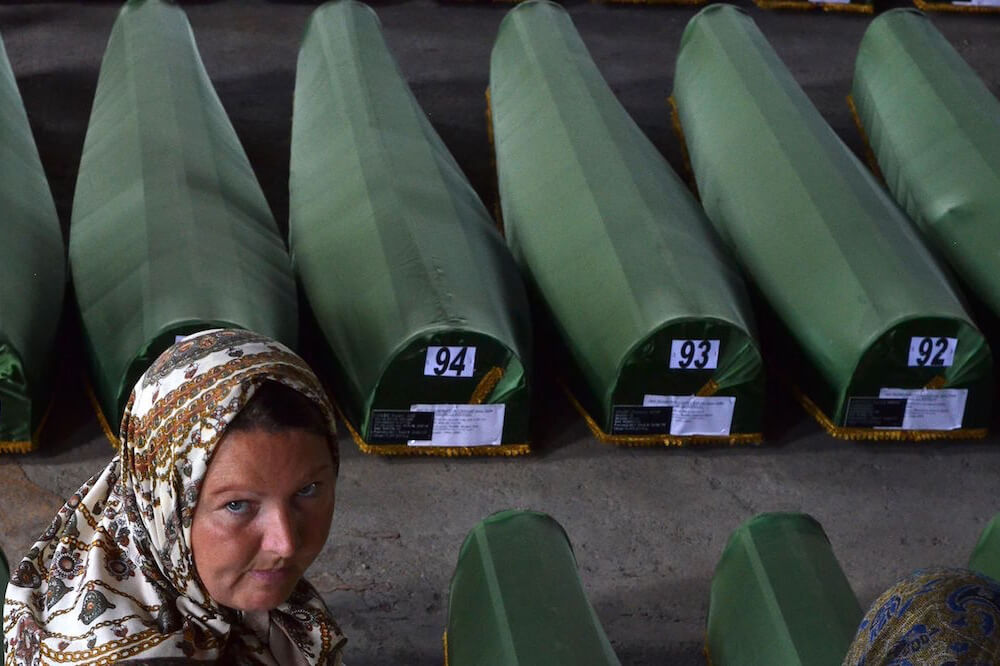 A survivor of the Srebrenica 1995 massacre searches for remains of her relative among body caskets laid out for burial. Photo: SBS News