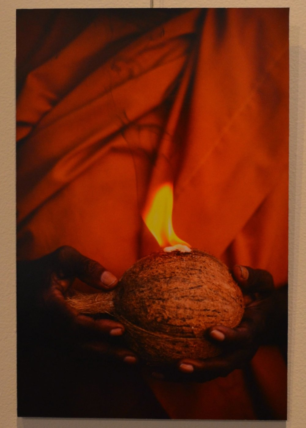 Buddhist nun holding a coconut and burning camphor at Kataragama. Photo: Dominic Sansoni