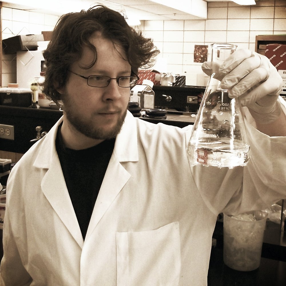 Rory in the lab holding a mitochondrial buffer solution (so, only mostly water)
