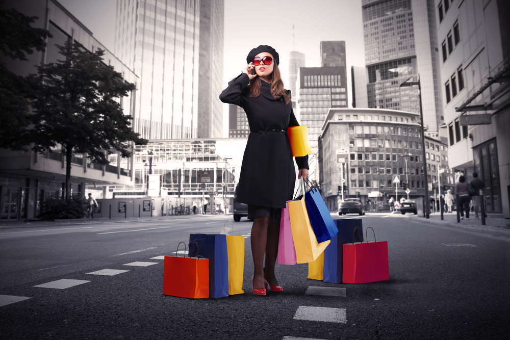 stock-photo-attractive-woman-using-a-mobile-phone-and-carrying-some-shopping-bags-on-a-city-street-61950070.jpg