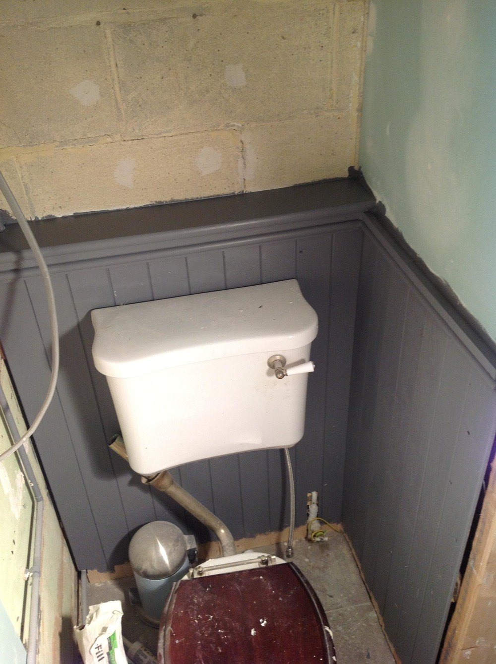 A new toilet cistern was attached to painted wooden paneling to configure with the old drainage.