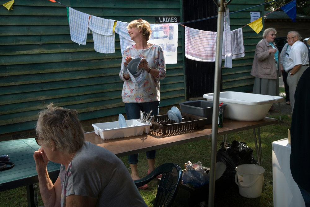 Copy of Ebernoe Horn Fair West Sussex, UK 2015. Tea tent lady washing and drying dishes.
