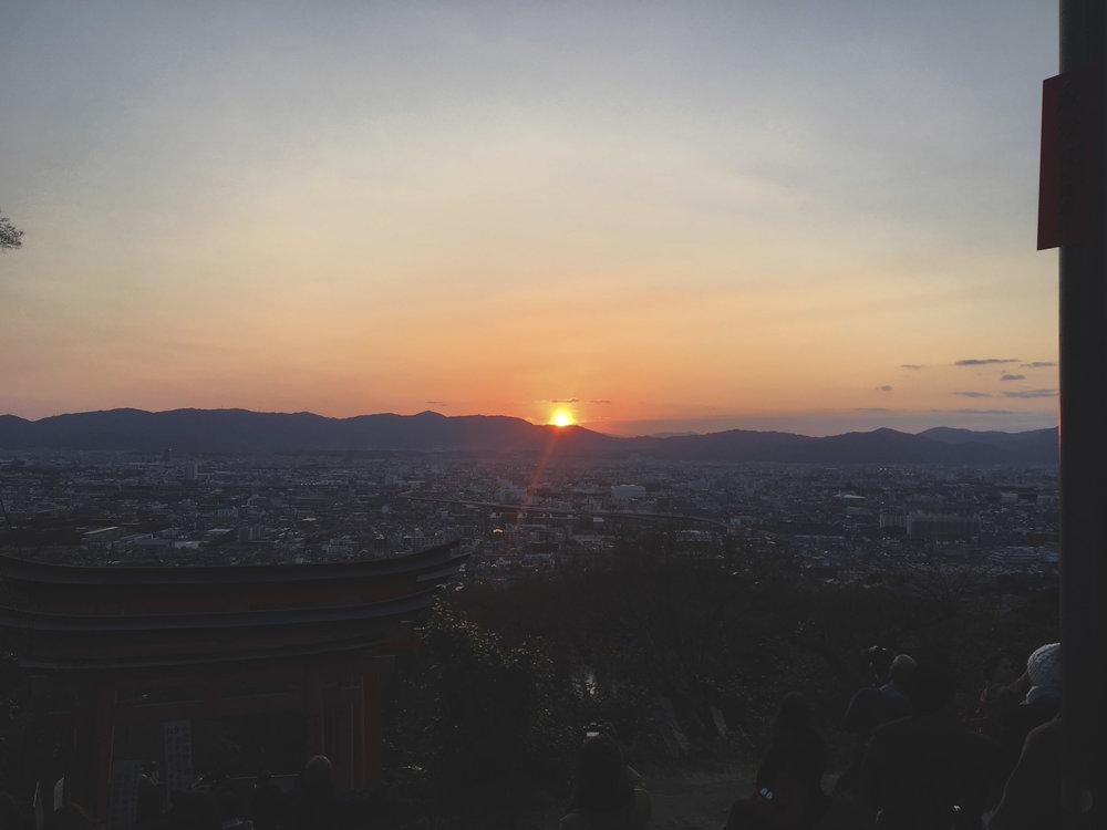 Pôr do sol do alto do santuário com vista para a cidade de Kyoto.
