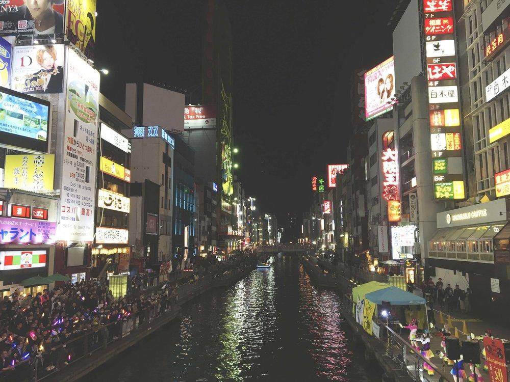 Show de J-Pop na margem do rio da cidade. Do lado direito estão as garotas com roupas coloridas que dublavam músicas super animadas para o público localizado no lado oposto que sabiam todas as letras e vibravam a cada performance.