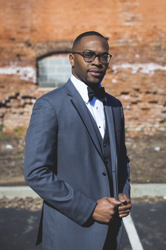 Groom poses in front of the beautiful exposed brick at the Cotton Room in Durham, North Carolina.