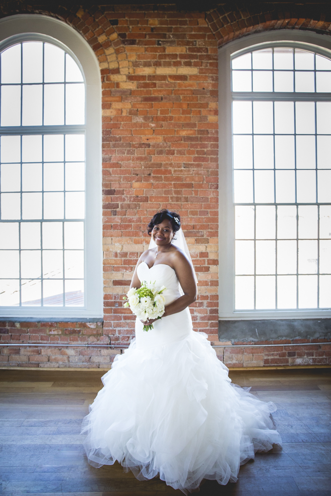 Bride poses in front of the beautiful exposed brick at the Cotton Room in Durham, North Carolina in a gorgeous wedding dress.