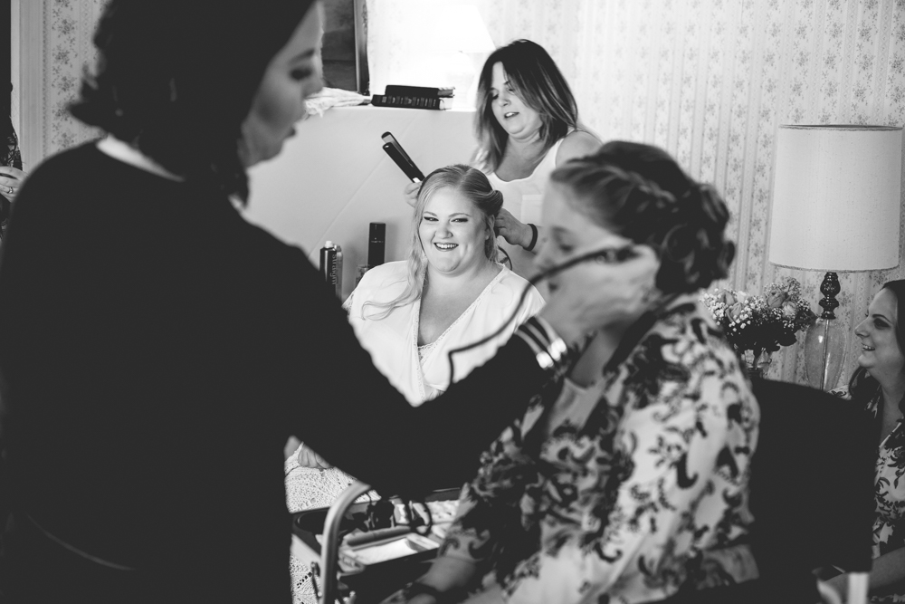 Bride watches as her daughter gets makeup before the wedding.