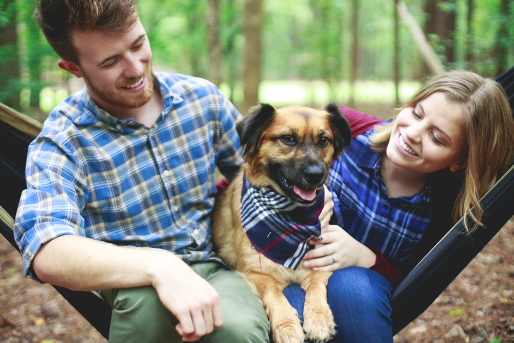 Celeste and Blake look down at their dog Yukon, who may just be the best dog model in the world. This photo was taken at William B. Umstead State Park, in Raleigh North Carolina for a camping themed engagement session.