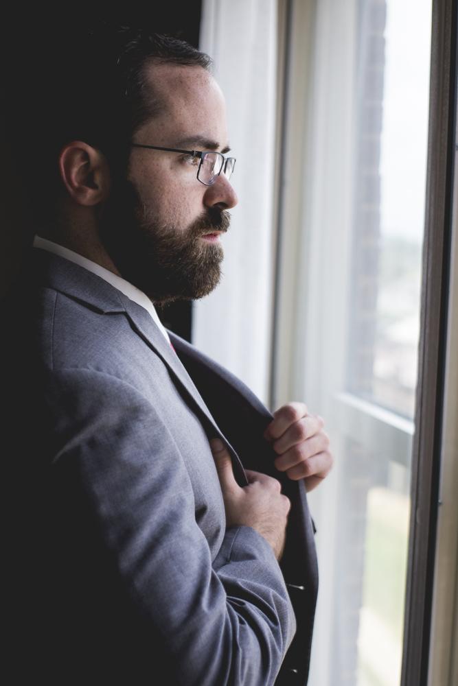 groom-looking-out-window-before-wedding