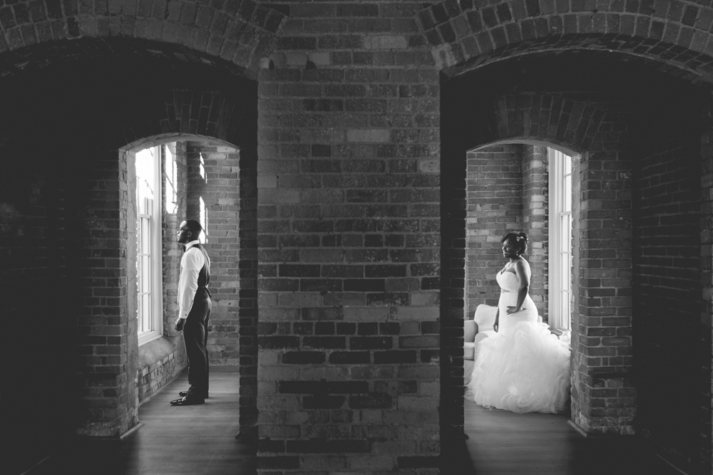 Brittany looks over at her future husband before their wedding ceremony. Photo taken at the Cotton Room in Durham, North Carolina. The Cotton Room is an event venue located in Durham's Historic Mill. The event space is set on hardwood rustic floors, set against an elegant exposed brick backdrop.