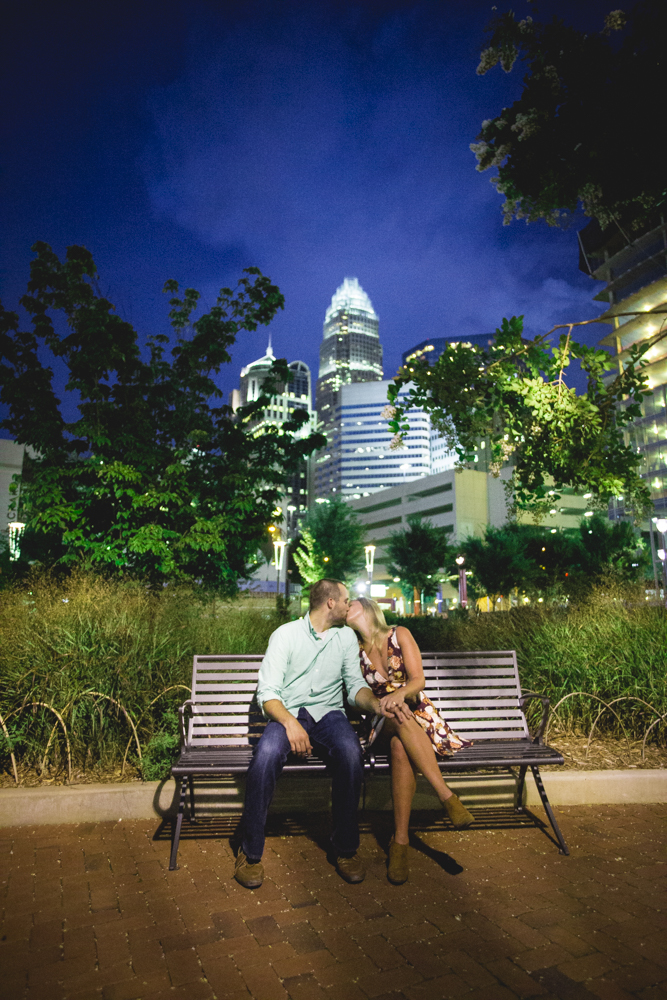 Couple kisses on bench in Uptown Charlotte with the city skyline in the background, during their engagement session.