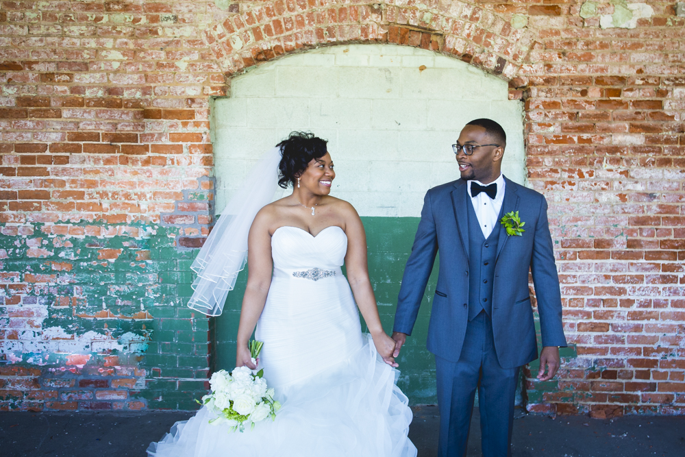 This crazy painted exposed brick at Belt Line Station Wedding Venue made for a perfect backdrop for bride & groom portraits.