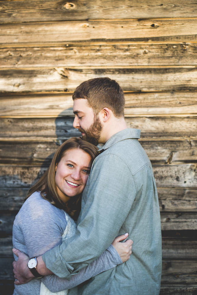 engaged-couple-against-barn-wood-planks