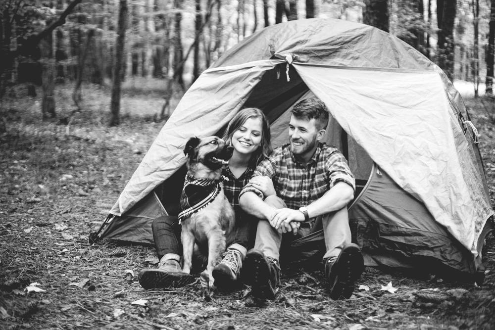 Celeste & Blake cozy up with their dog Yukon, during their camping themed engagement session at Raleigh's Umstead State Park.