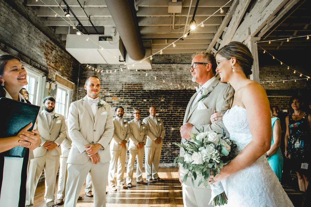 Daniel K. Photography captures a photograph of a groom as he waits for his bride as she walks down the aisle at The Stockroom 230 in Raleigh, NC.