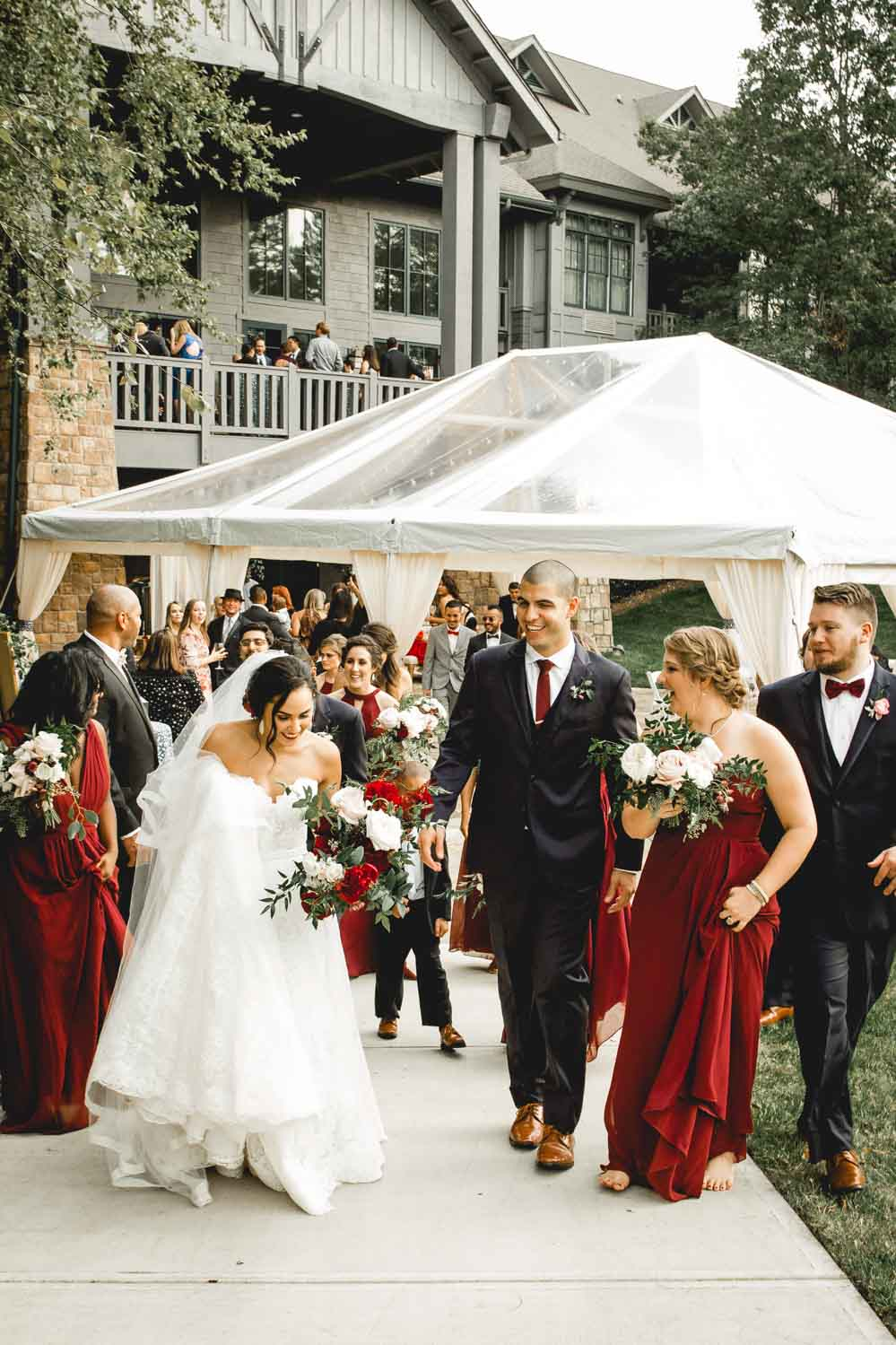 Photograph of a bride & groom and their wedding guests shortly after their outdoor wedding ceremony at the gorgeous Ballantyne Lodge & Hotel in Charlotte, North Carolina.