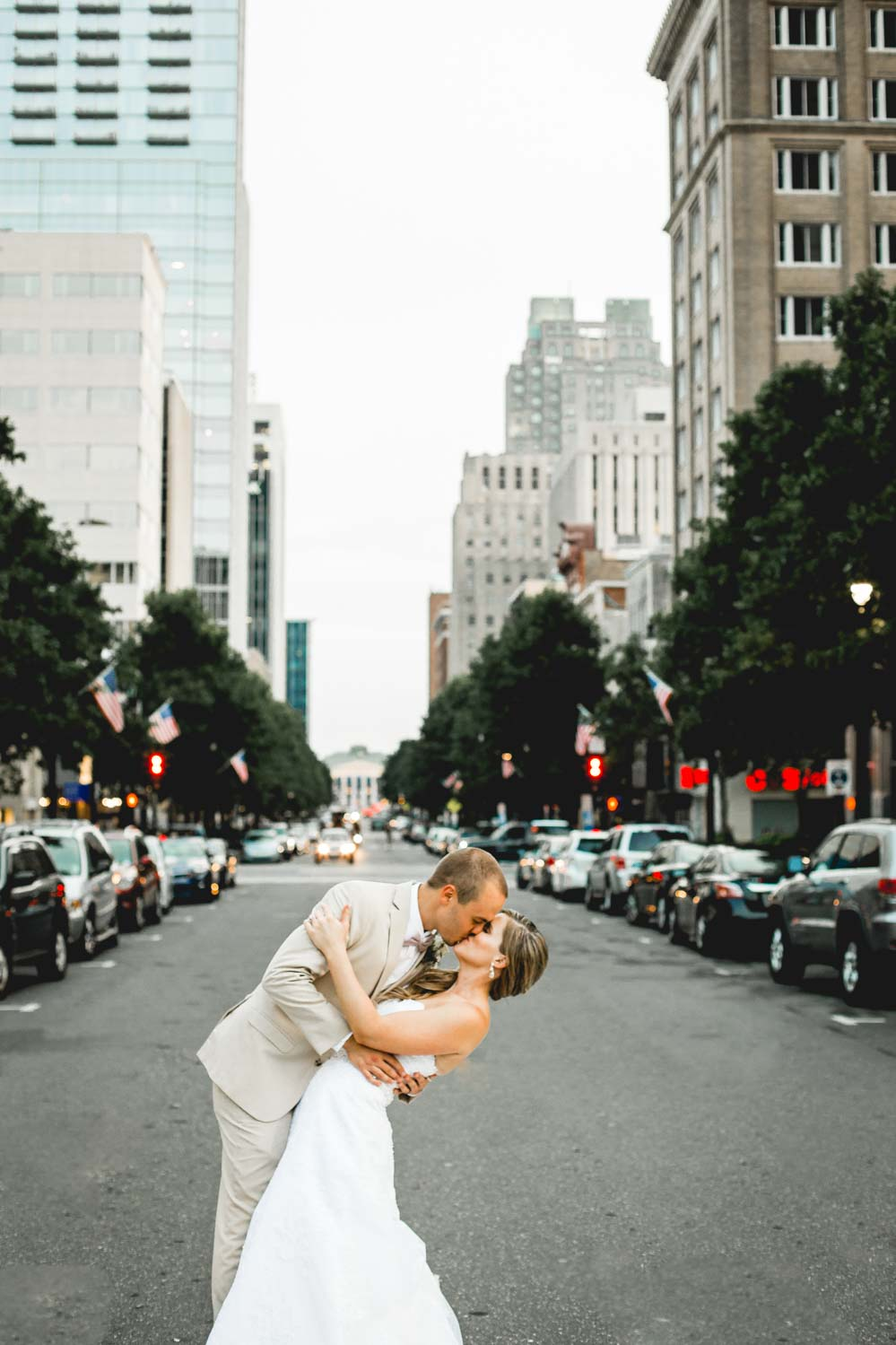 A just married couple kisses in the streets of downtown Raleigh for their wedding photos. Their wedding venue was held at the Stockroom 230 which is in the heart of downtown!