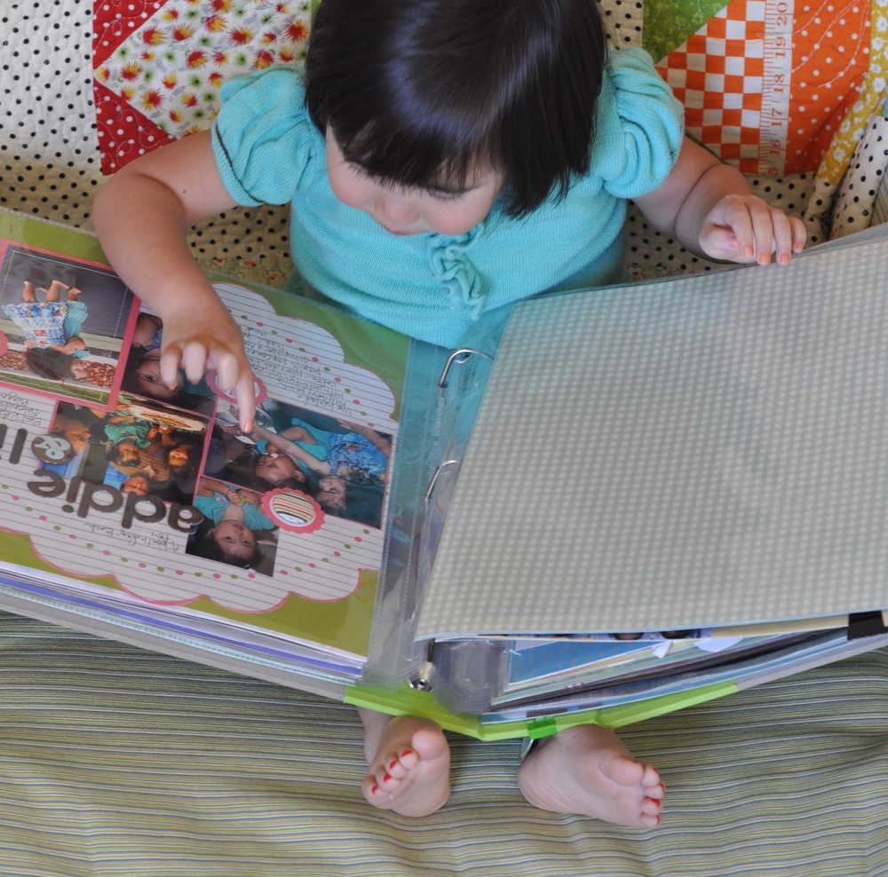 Miss Addie (a few years ago) enjoying her All About Addie scrapbook in our family Library of Memories.