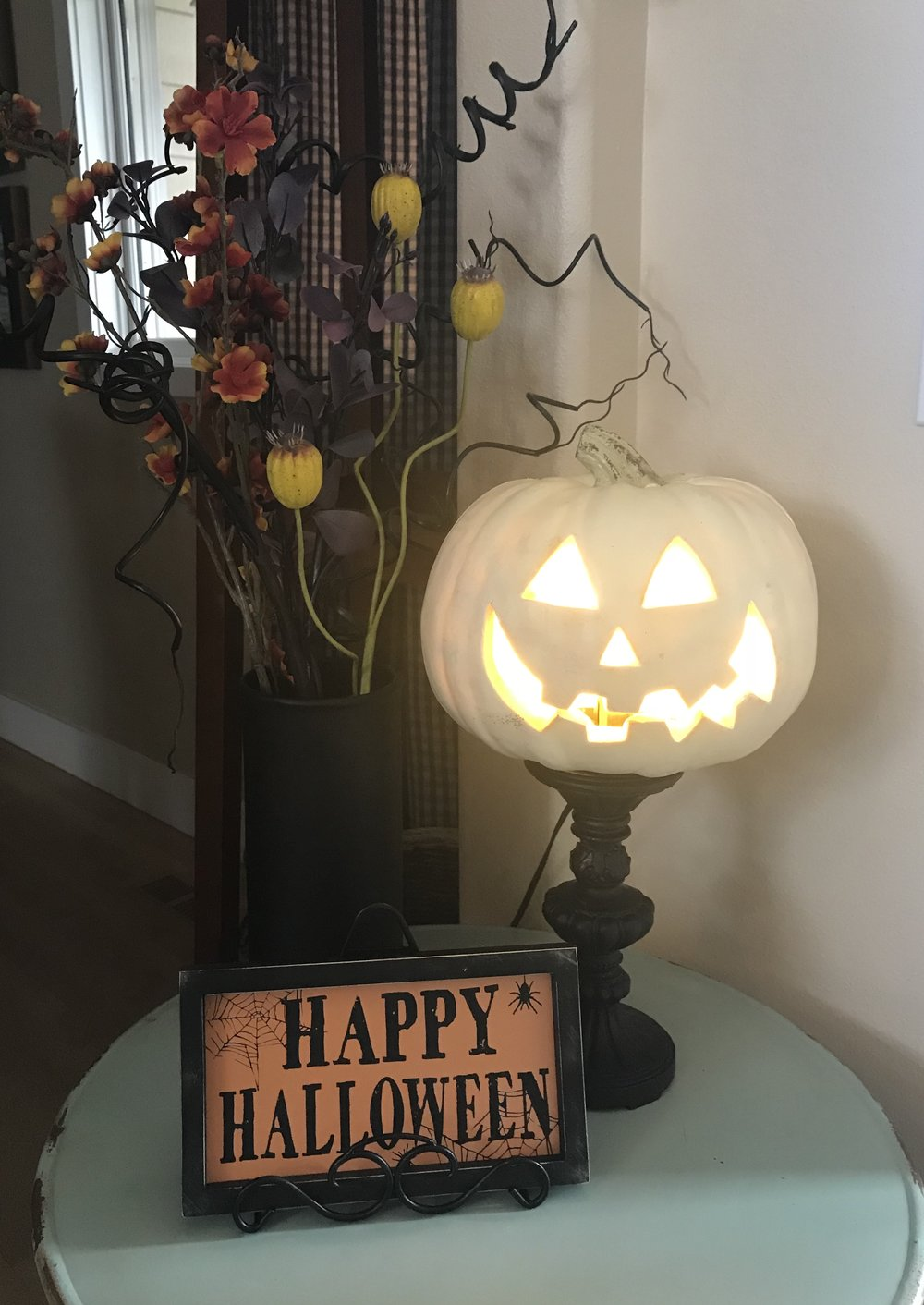 This lighted jack-o-lantern is old, but I decided to pull up my little turquoise table and create a cute little corner by the front door.