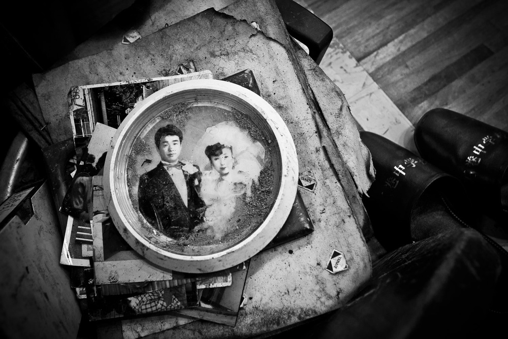 Ishinomaki, Japan, 2011. In the corner of yet another evacuation center, in a pile of orphaned photos and notes found in the mud and debris, a newlywed couple stares into a future turned upside down. Their frame and glass still covered in dry mud from a disaster hitting like a lightning from the sky.