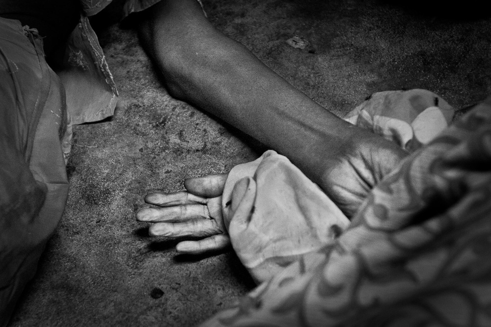 Port-au-Prince, Haiti, 2010. Separated by death, but still as if reaching for each other, bodies lie on the concrete floor of the hospital morgue after the 7.0 earthquake that hit on January 12.