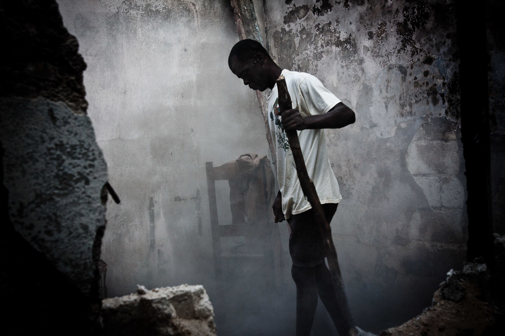 In a cloud of dust a wall collapses in a back-alley in Port-au-Prince as the rebuilding process slowly begins. The work is extremely dangerous and casualties are high due to the unstable remaining buildings and complete lack of safety equipment.