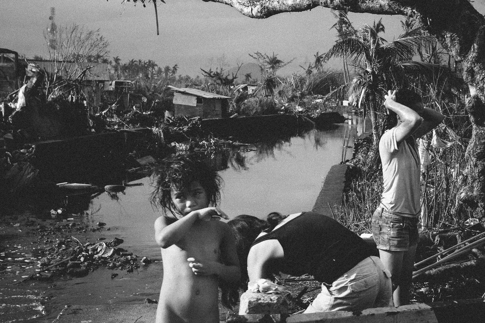 Leyte Province. With water from a broken pipe, three girls are washing themselves in the early morning light before the scorching heat sets in.